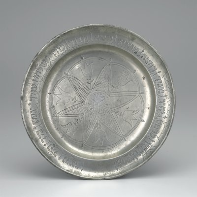 pewter plate with floral and fish motifs in center and Hebrew around outer edge