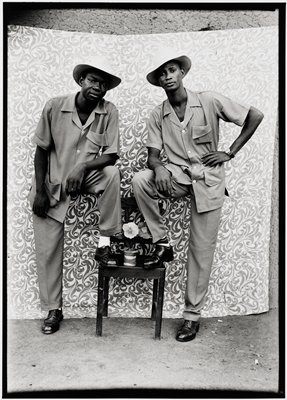 two friends dressed in three-pocket bush suits with pith helmets imitating the actor Eddy Constantine; both men stand with one foot on a small table leaning on their knee