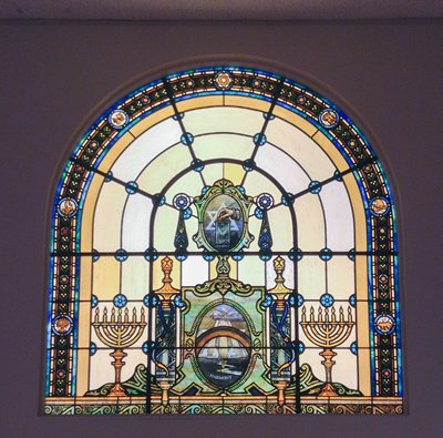 half-circle shape; yellow and swirled green glass; central oval Star of David medallion with floral pendants; ship, star, snake, unicorn in cartouches around edges; frameless