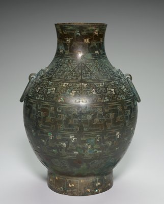 "bulb shaped with ring handles; handles held on by hardware with animal-like ""face""; incised pattern covers entire vessel; vessle is green with areas of white showing through the pattern"