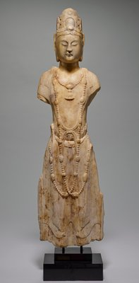 Standing Bodhisattva of white marble, arms broken off below shoulder. The figure wears a narrow scarf, barely defined, and a skirt girdled at the waist, its upper edge finished with a curling line. Jewelled necklace and long chains. High headdress. Feet missing, head restored at throat where formerly broken off.