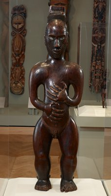 carved wood, standing male figure; hair bound in a topknot; inlaid paua shell eyes; larger scale head, face adorned with tattooing; arms akimbo and large hands spread over abdomen; raised disc belly button; erect penis; raffia loin cloth in separate vitrine