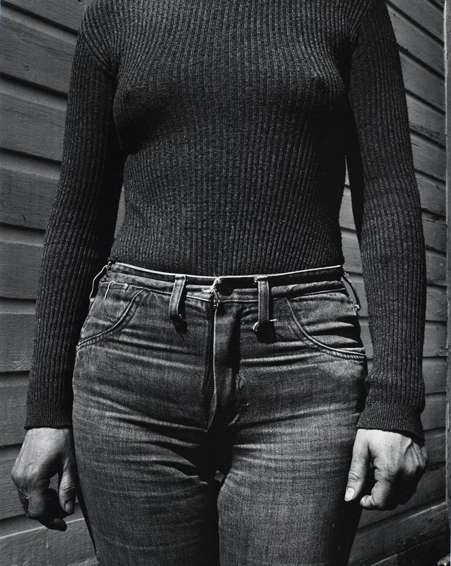 torso of a woman wearing a tight-ribbed sweater and tight jeans