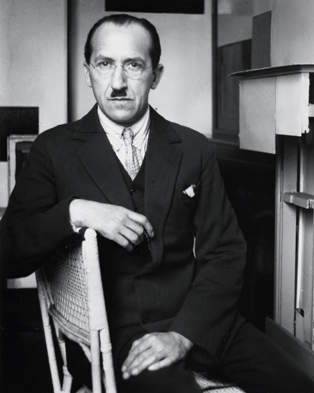 seated man wearing three-piece suit and round glasses, with receding hairline and small moustache; wicker chair