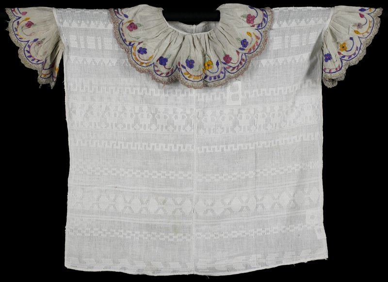 white body with subtle woven designs; ruffled neckline and sleeve fabric in light grey, edged in scalloped crochet and embroidered in purple, green, yellow and pinks with floral designs