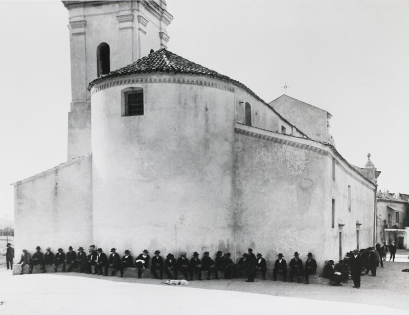line of men wearing dark hats and suits, seated on a step along the outer walls of a church; dog, lying down, in front of men near bottom center