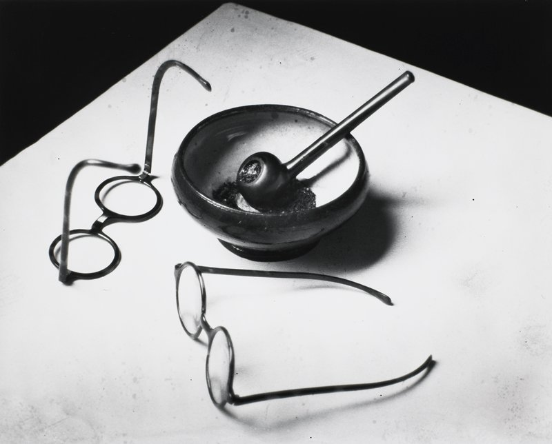 two pairs of round, plastic-framed glasses and a pipe in a small bowl of ashes