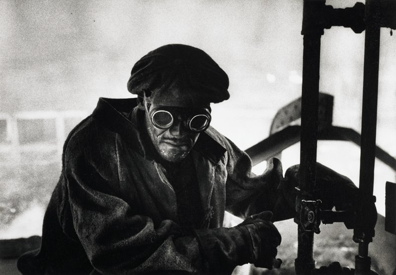 worker in heavy jacket, gloves, cap, wearing goggles; hands near pipes on right