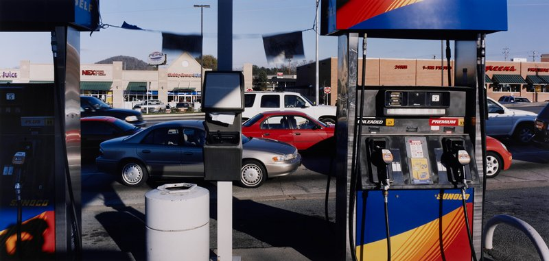 gas pumps at a gas station; cars on busy street behind pumps; strip mall at left behind cars, Walgreen's at right
