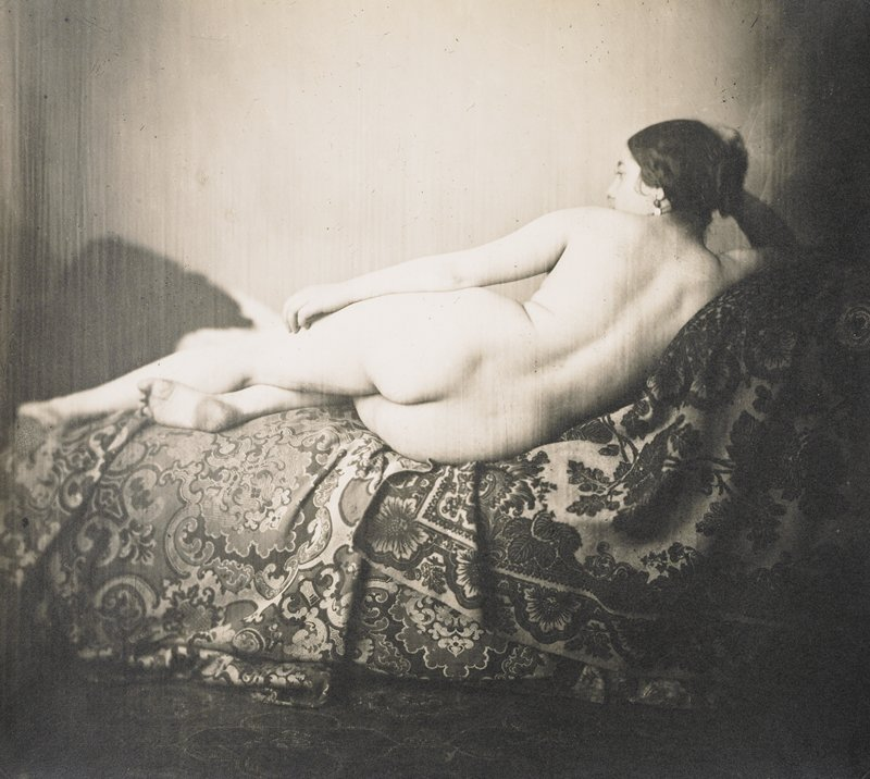 female nude lying on side on a couch facing away from the camera, head propped on hand; elaborately woven(?) fabric on couch
