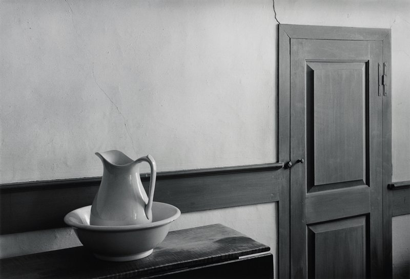 pitcher in bowl on stand with closed door to the right; large crack in wall at upper right corner of door (see L2005.262.227 - same image, smaller size)