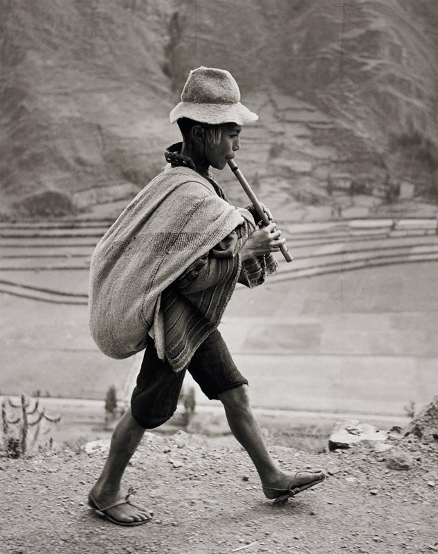 boy playing a flute, walking, carrying a bundle low on back