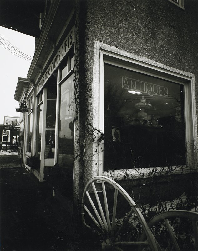 """corner of building, with side window with """"ANTIQUES"""" neon sign; two wagon wheels, LRC; storefront windows at L"""