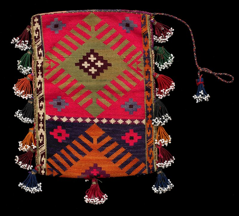 small rectangular pouch; multicolored cord with blue beaded tassel at top; eight multicolored yarn and bead tassels on sides and bottom; pouch woven with three stepped diamond motif designs in multicolors; gold metallic trims;(cresstitch)