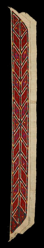 long embroidered strip, on two pieces of cream-colored fabric; predominately red and green; geometric designs of diamonds and triangles with repeating diamond borders