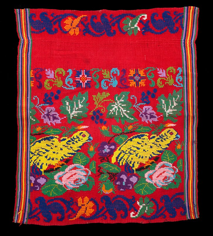small panel in bright multicolored threads; red ground; two yellow and blue birds on branches with pink roses and purple pansies; band of leaves; blue flower scrolls and multicolored organic band; stripes at sides