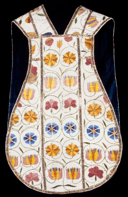 Chasuble of natural linen, embroidered in coarse laid work with tulips and pinks in shades of rose, yellow, blue and white, each flower encircled with its own stem. In center ofback much elongated standing Virgin and Child, also in coarse laid work. Coarse gilt braid edges and divides chasuble into sections.