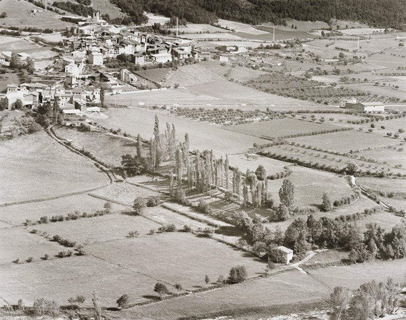 village UL; fields and a few buildings surrounding; road with six moving vehicles in top third of image