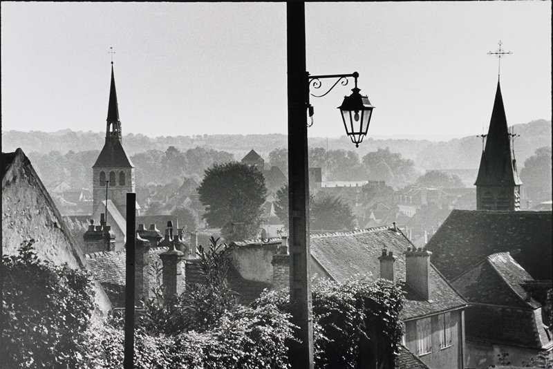 view of rooftops, trees and two steeples; street light center foreground