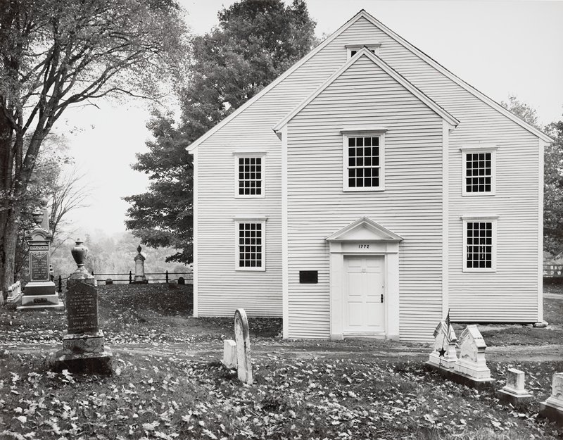 church surrounded by graveyard; narrow siding; doorway with 1772 above door; two windows in bottom row, three in second row and one above and behind peak of entryway