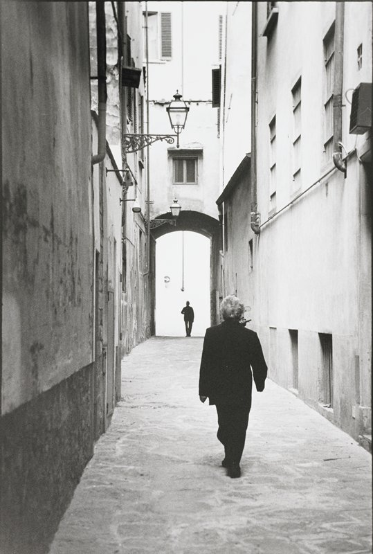alley with a male figure at the end and a female figure in the foreground walking away from camera; two decorative street lamps on left side buildings