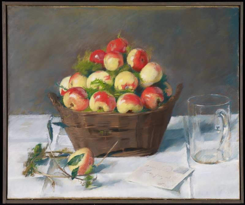 basket of red and yellow fruits with green leaves; one apple on table with stems at LLC; glass mug at R; letter on table at bottom R