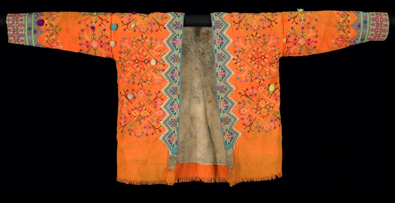orange with turquoise trim at cuffs and around opening; rectangular tightly-embroidered decorative flap with lime green top strip on back of neck; cross stitch embroidery overall with floral motifs in multicolors; scattered pompons; grey lining