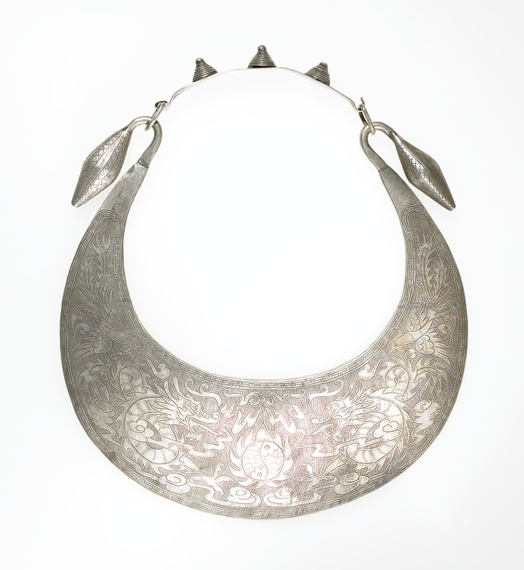 """semi-circular collar ending in hooks with football-like shaped ends; separate strip hooks onto loops attached to ends to complete closure; motifs on disc include 2 birds, 2 dragons and a double fish; edge motifs similar to """"Greek key"""" design; closure has 3 spiral beehive like shapes with small metal balls at top attached"""