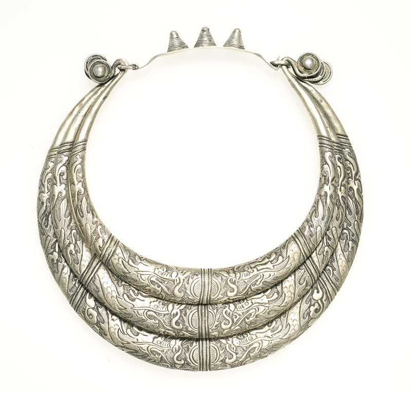 torque made from three rings of hollow silver; each ring ends in curlicues; rings are decorated with four panels; each panel has a different part of two dragons; dragon's faces meet in the middle; sun symbol at the very center; connecting piece is solid silver with three cones on it
