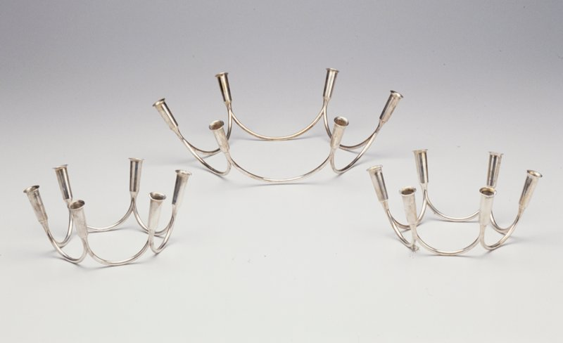 Six half-circles of thick silver wire connected together with candle cup at each of six points