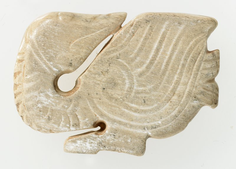 Pendant (plaque) in silhouette form of a goose with incision and relief. Ivory colored jade, calcified; trace of red pigment. Both sides identically decorated with double line relief; the eyes and the beak are indicated by incised lines.