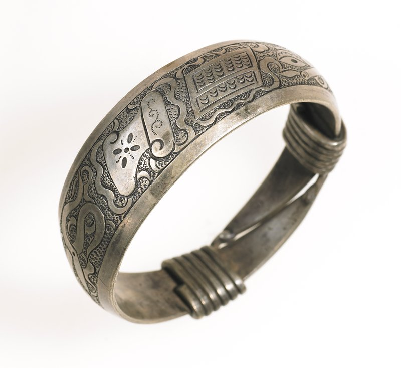 bracelet with thick silver piece curved into a circle; ends are wrapped in square silver wire; front of bracelet has a spoon-like object, scissors, a scroll object, a washboard object and a bowl, and a paint brush; background of dots and ribbon; leftovers of a tag on the inside of the bracelet