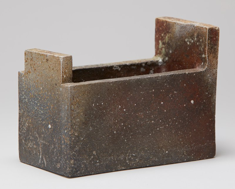 rectangular form with flat bottom; square corners; straight sides; tops of short ends taller than tops of long sides; browns, tan, reddish-brown with white and light green spots
