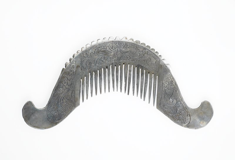 hair comb made from a flat sheet of silver; comb is a half circle with the edges curving away from the center; bristles at the very center; top of cone has ridges and rounded border; three panels on each side; Side 1: phoenix-like bird on left, dragon on right and butterfly over the bristles; Side 2: bird on left, butterfly over bristles, and snake-like dragon on right
