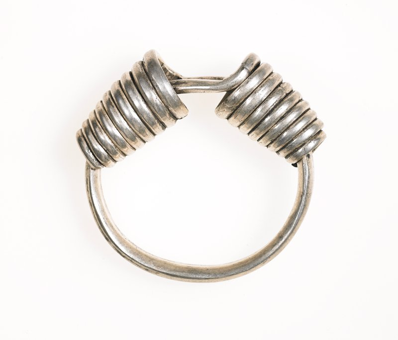 bracelet; circle formed by one long piece of silver; twisted at ends to wrap the circle