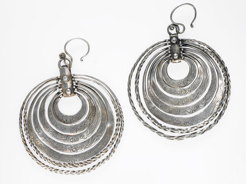 pair of earrings; each has seven hoops attached by a rectangular plaque; plaque attached by a loop to the ear piece; the first five of the hoops have a double fish in the center and a fish on either side; largest two hoops are twisted wire