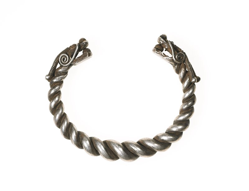 one of a pair of bracelets; bracelet is loop of heavy, twisted wire; each end has a dragon head on it; dragons have a sphere in between their jaws; two curlicue whiskers on each dragon; two large antennas made from coiled wire with a sphere on the end rest on top of each dragon head