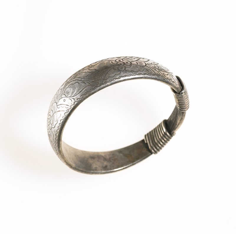 one of a pair of bracelets; hoop of thick, silver wire; thin wire is wrapped around where the hoop attaches to itself; floral pattern with three large flowers and leafy background is etched on the hoop