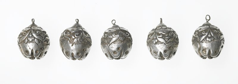 ornament bell, bell is sphere-shaped with flower pattern on sides and top; top has a tiny ring to attach bell to other ornaments; bottom has flat points and six crevices in a star shape; two of the cuts are longer than the rest and run half way up the sides of the bell