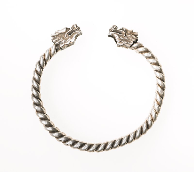 one of a pair, bracelet has two rows of twisted wire; wire is twisted in different directions so the wire looks like it is braided; dragon heads on both ends
