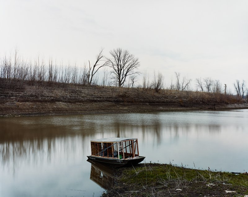 small boat with a structure--seats under structure; on bank of water; bare trees on horizon line