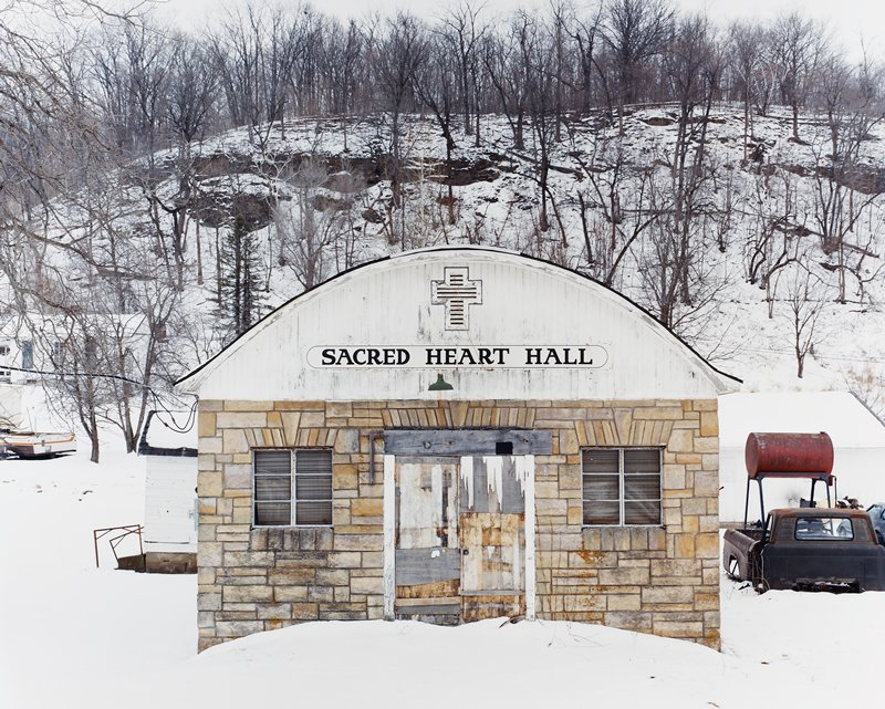 "stone building with worn wood doors; rounded roof; ""SACRED HEART HALL"" sign above door; rusty truck at right; snowy"