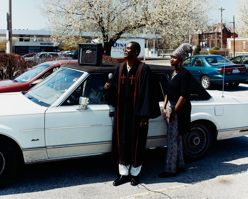 black man wearing black and red clerical robe holding a microphone, next to a white car; young black woman wearing turban and slacks with snakeskin print and long black jacket; in parking lot