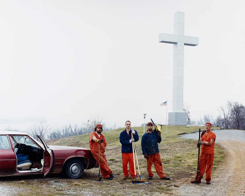 four men wearing orange scrubs and denim jackets with lawn tools; car at left; large cross in background