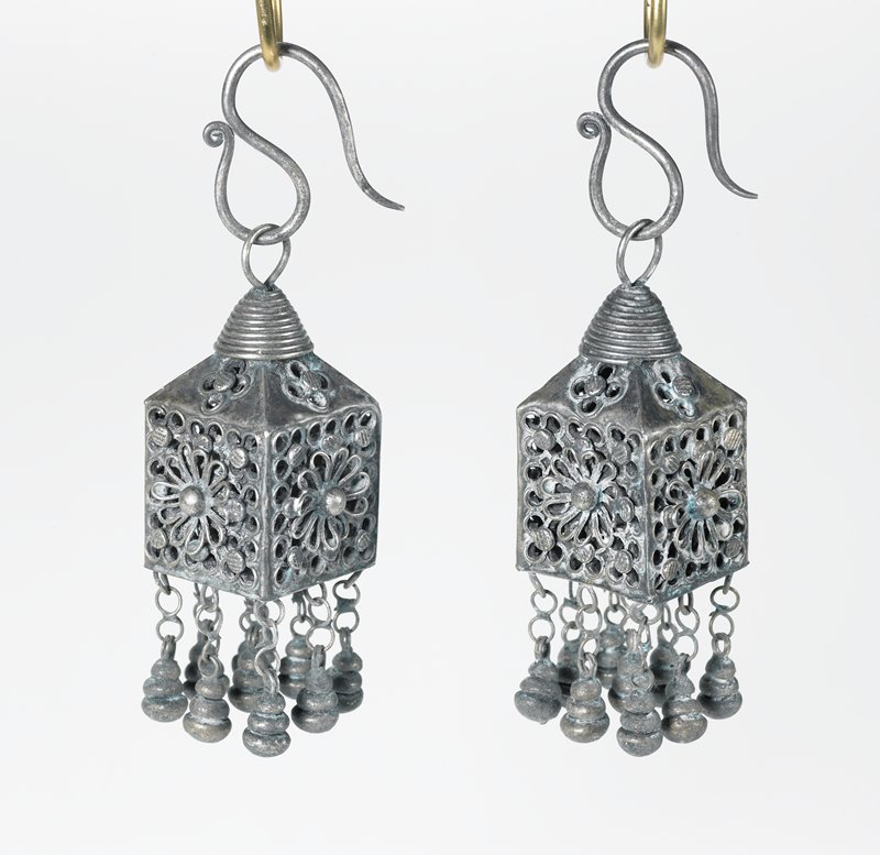 pair of earrings, each is a box with circular holes in it; a flower decorates each side; box top has a cone on it; ear piece attaches to the cone by a loop; bottom of the box has eight, three-tiered ornaments hanging from it in two rows