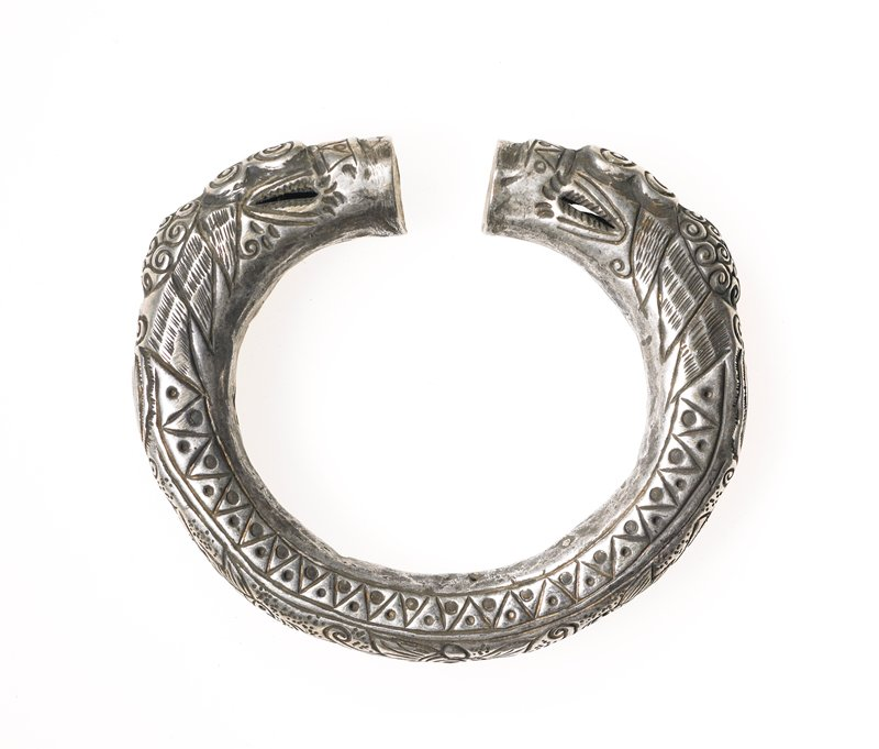 dragon bracelet; blunt jaw ends; hollow; multiple spiral designs on and behind head; central floral motif with fish and bird motifs between flower and head; sides, triangles in alternating directions, have dot in center of each
