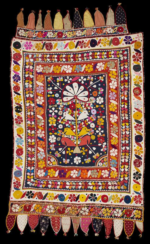 appliqué overall in various brightly -colored solid color and printed fabrics; flower and leaf bands around edges; central Tree of Life motif on dark blue with three pairs of birds-pink, white and yellow; lappet panels at top and bottom