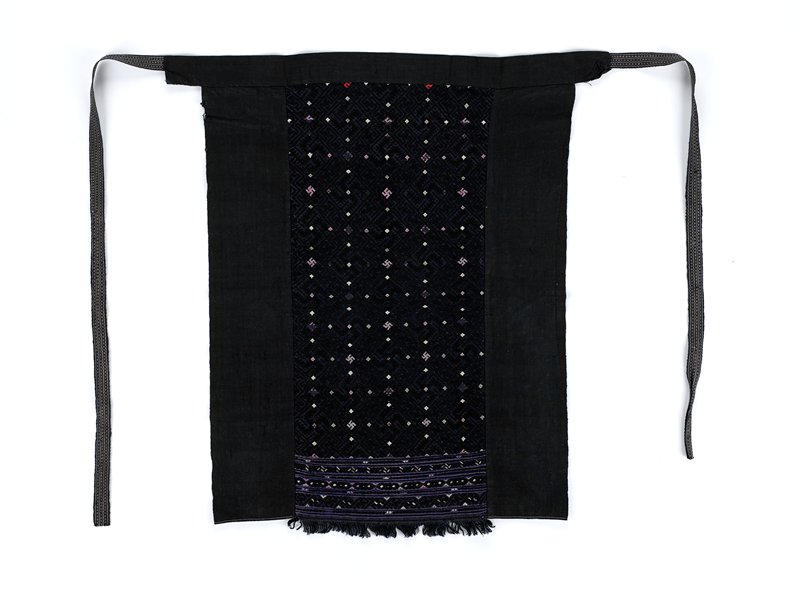black sides and waistband; dark blue, tan and white woven ties; center panel of dark blue and purple embroidered with black swastika motifs highlighted in pink, cream and green, and horizontal linear, swastika and repeating geometric patterns at bottom; short fringe on embroidered panel bottom