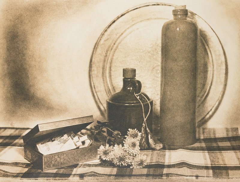 still life with small wooden box containing package of Chesterfield cigarettes, small bunch of marigolds, jug with tassels on handle, tall vase with cork in neck and round plate on a plaid cloth