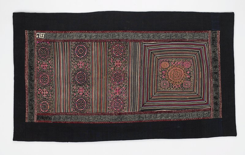 apron sewn as a panel, edged and backed in dark blue fabric; central panel edged in bands of cream with black, grey and dark purple swastika-key designs, trimmed in maroon; central appliqué and embroidered rectangular panel in predominately pink embroidery with roundels, scrolls and floral shapes and linear appliqués of various colored fabrics